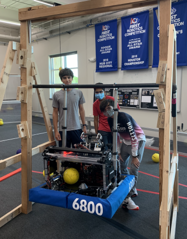Andrew Cloran[left], Shaunak Pandey[middle], and Andrew Escott[right] pose next to their robot